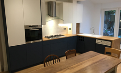 A stunning contemporary kitchen with a wooden worktop, black base cabinets and white wall cabinets