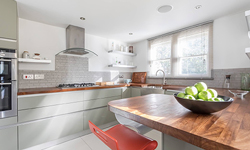A large contemporary kitchen with neutral cabinets and an iroko worktop