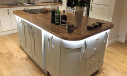 A stunning contemporary kitchen island with a wooden worktop, white cabinets and under-worktop lighting