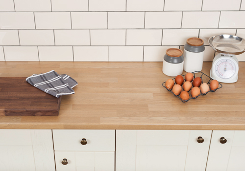 A traditional kitchen with an oak laminate worktop and a splashback made of white subway tiles