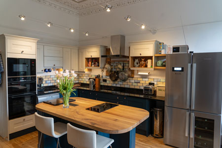 This L-shaped kitchen features an island with a full stave oak worktop.