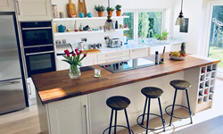 A contemporary kitchen with neutral cabinets and an American walnut worktop