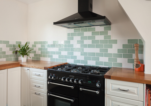 A neutral kitchen with a splashback made of green and white subway tiles