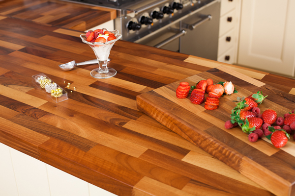 A walnut worktop with a chopping board, strawberries and a sundae glass