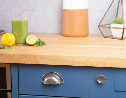 Close view of a Prime Oak worktop, with several decorative aspects including a green smoothie and wire candle holder.