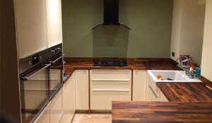 The contrast of dark worktops with light units adds depth to smaller kitchens.
