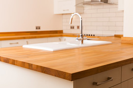 Cherry worktops add an incredible sense of warmth to this beautiful kitchen, counterbalancing the cool surfaces of the ceramic sink and tiling.