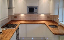 Oak worktops customised with a bespoke sink cut out and fanned drainage grooves.