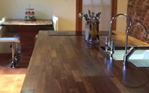 Elegant black oak worktops on a kitchen island featuring a pencil edge profile and irregular corner cuts.
