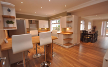 Oak worktops used to great effect for shelving and as a breakfast bar.