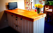 Beech worktop used as a chunky room divider between kitchen and dining room.