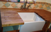 Oak worktop with chunky drainage grooves and Belfast sink cut out.