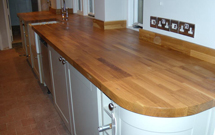 Prime oak worktops with radius corners, Belfast sink cut out and matching upstands.