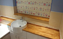 Oak worktops used to great effect as a bathroom countertop and as bath trim.