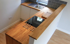 Oak worktops cut to accommodate an over-mounted sink and electric hob.