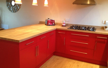 Oak worktops alongside bright red cabinetry create quite a statement.