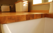 Close-up of an oak worktop with Belfast sink cut-out.
