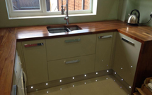 Exquisite iroko worktops with a double-sink cut out and drainage grooves.