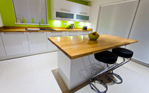 Prime oak worktops look stunning in this glossy white, modern kitchen.