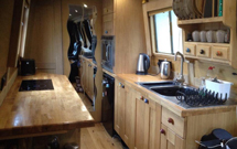 Traditional oak worktops work perfectly in a narrow kitchen too, as shown in this canal boat's galley.