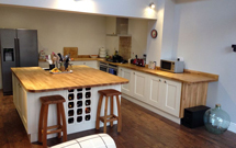 Prime oak was fabricated to create a vast kitchen island with a Belfast sink cut out.