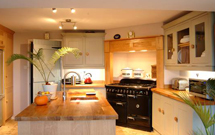 Prime oak worktops create a stunning  island in this contemporary farmhouse kitchen.