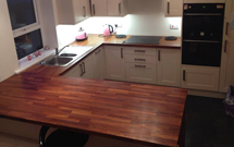 Extra wide iroko worktops make great use as a worktop and breakfast bar.
