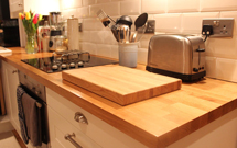 Oak worktops with cut-outs for a sink and hob. Offcut used as a chopping board.
