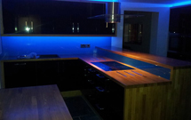 Oak takes centre stage in this futuristic kitchen, lit by plenty of blue LEDs.