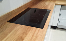 An induction hob set into a full stave oak worktop with an oven hob cut-out.