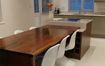 Our full stave American walnut worktops were used to create a dining table right in the heart of this modern kitchen.