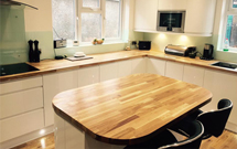 An oak kitchen with an island featuring smooth radius corners.