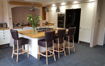 This kitchen has an expansive oak worktop at the heart of it - a perfect space for socialising whilst cooking.