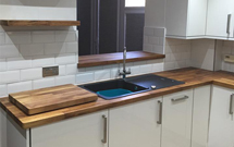 Walnut worktops look simply stunning alongside glossy white cabinets and other modern features.