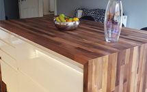 Walnut worktops used to great effect on the top and sides of a kitchen island.