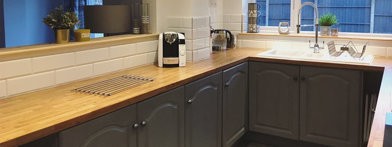 A kitchen with a Colmar Oak effect laminate worktop and dark cabinets.