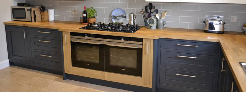 A solid wood kitchen with oak worktop, double oven and hob.