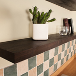 Black oak is a dark and luxurious material, making it ideal for hardwood floating shelves in a modern kitchen.