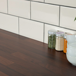 Black walnut block laminate worktops can be matched with a range of different wall colours and materials, like these white metro tiles.