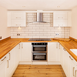 Cherry worktops are a warm surface that adds great character to any kitchen - even against stark white colour schemes such as this.