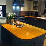 A bespoke caramel bamboo breakfast bar, featuring 2 large radius corners to match the curved corner cabinets below.