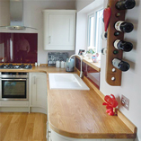 Bespoke fabricated full stave Prime Oak worktops are the ideal complement for this modern, curvy kitchen.