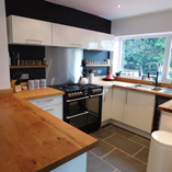 In this kitchen, the contemporary kitchen cabinet doors and handles complements the square edge, full stave oak worktops