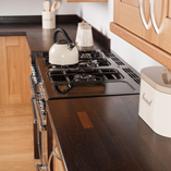 The dark colour of the wenge worktop contrasts beautifully with paler wood and white walls.