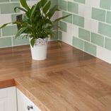 Deluxe oak worktops were the perfect choice for this classic white kitchen. A Deluxe stave is used as an end panel to protect the worktops from the oven's heat.