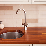 This iroko worktop had a custom circular undermounted sink cut out made by our bespoke worktops service.