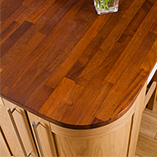 An iroko kitchen island worktop featuring large radius corners to match curved cabinets.