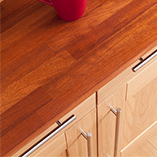 Iroko worktops in a Shaker kitchen with oak kitchen cabinets and stainless steel bar handles.