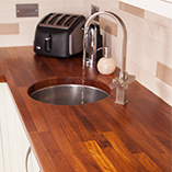 An iroko worktop with custom circular undermounted sink cut out and corresponding tap hole.