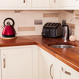 Iroko worktops with a soft profile edge and small radius corner in a modern Shaker kitchen.